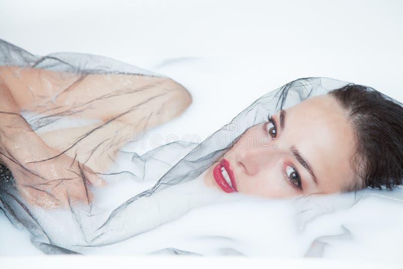 Portrait créatif de femme sensuelle avec Tulle noir dans le bain de lait photo libre de droits