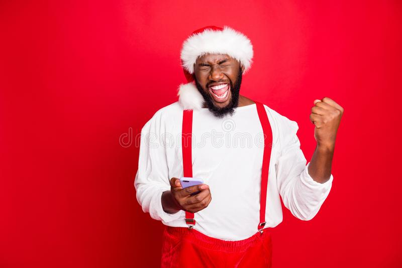 Portrait of crazy african christmas father raising fists screaming yes got noel news like holding cell phone wearing hat stock photos