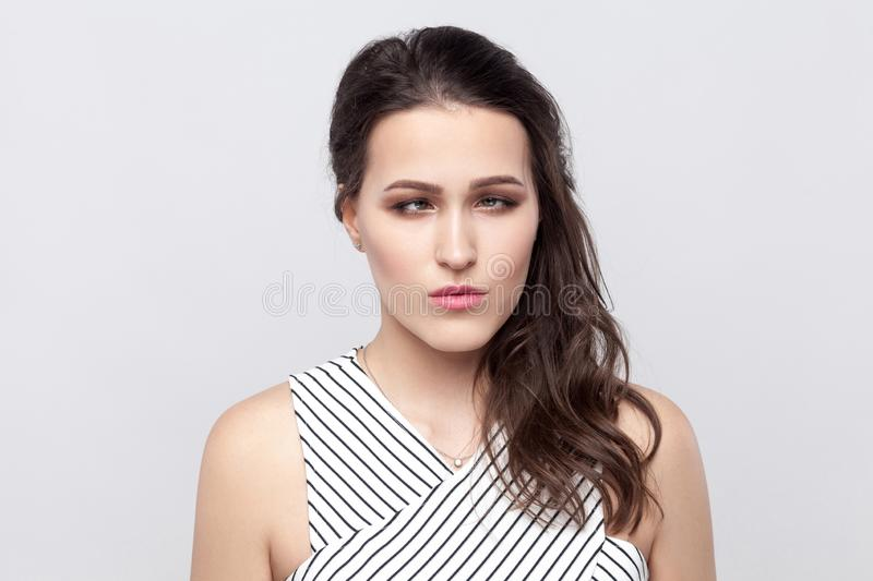Portrait of crazy funny beautiful young brunette woman with makeup and striped dress standing and looking at camera with crossed royalty free stock image