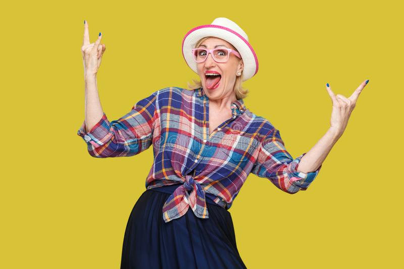 Portrait of crazy funny modern stylish mature woman in casual style with hat and eyeglasses standing, screaming and looking at. Camera with rock sign. indoor stock photo