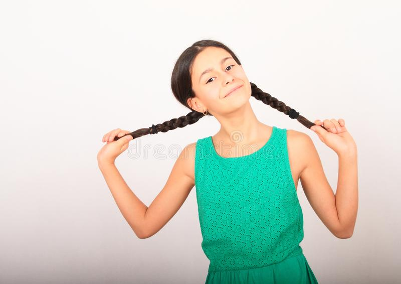 Portrait of crazy pretty girl holding braids. Portrait of smiling pretty girl - crazy brunette kid holding her two braids, dressed in green dress. Childhood royalty free stock photos