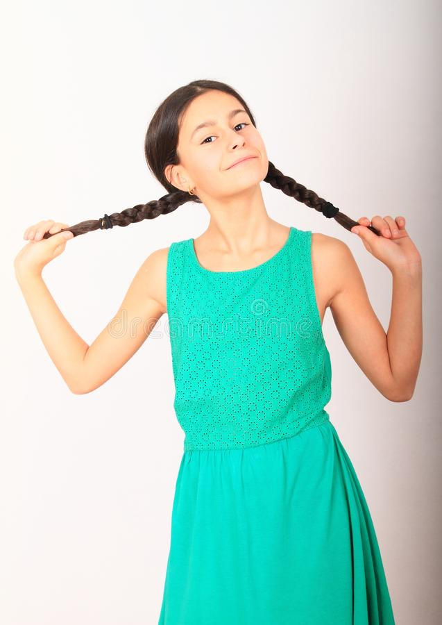 Portrait of crazy pretty girl holding braids. Portrait of smiling pretty girl - crazy brunette kid holding her two braids, dressed in green dress. Childhood royalty free stock images