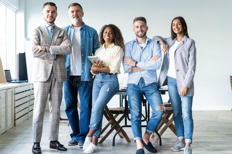 Portrait of creative business team standing together and laughing. Multiracial business people together at startup royalty free stock photo