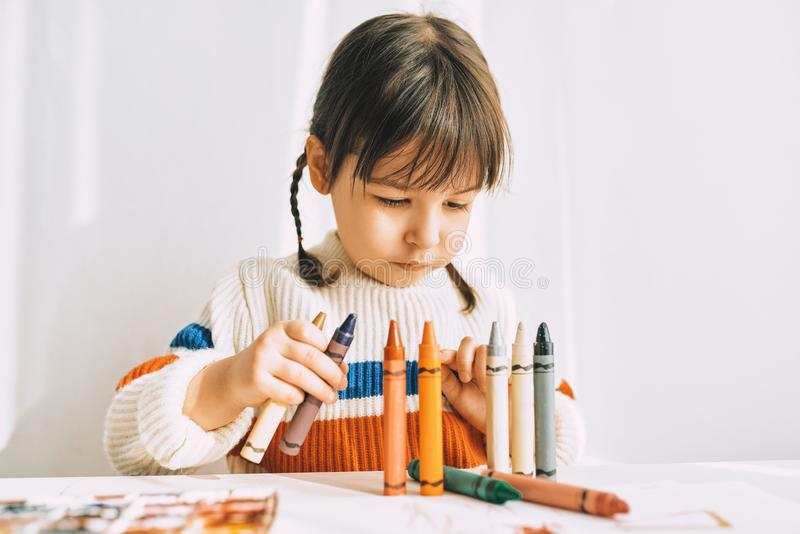 Portrait of creative cute little girl playing with oil pencils, sitting at white desk at home. Pretty preschool kid draws royalty free stock photos
