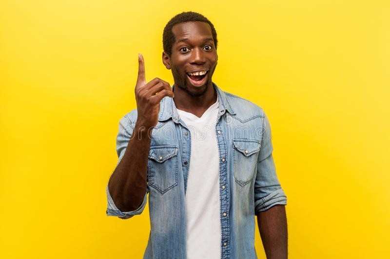 Portrait of creative inspired man pointing finger up, showing great idea sign. studio shot isolated on yellow background royalty free stock photography