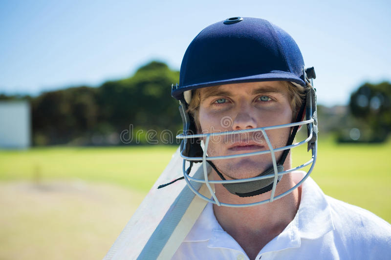 Portrait of cricket player holding bat while wearing helmet at field. On sunny day stock photos