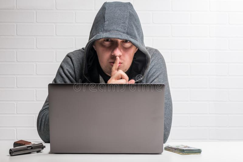 Portrait of a criminal hacker with a notebook, weapon and money concept royalty free stock photo