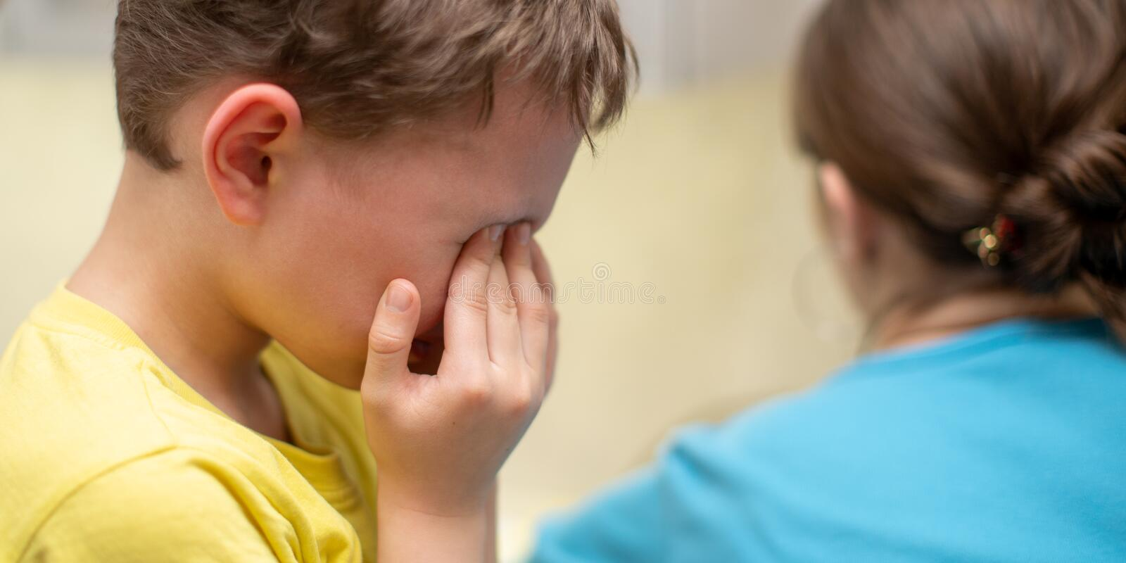 Portrait of a crying boy on a white background stock photo