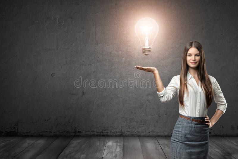 Portrait cultivé d'une jeune femme d'affaires tenant la grande ampoule rougeoyante photographie stock libre de droits