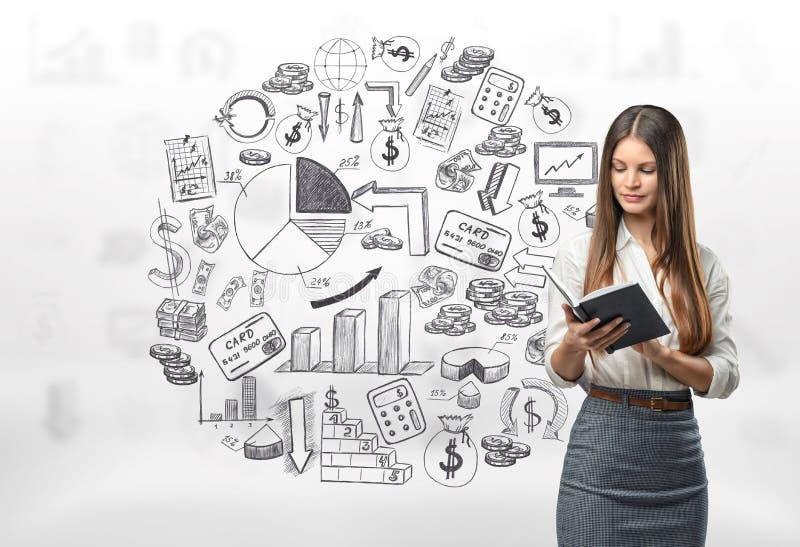 Portrait cultivé de jeune femme d'affaires regardant dans son carnet image stock