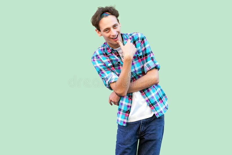 Portrait of cunning young man in casual blue checkered shirt and headband standing and looking at camera with cheating face and royalty free stock photo