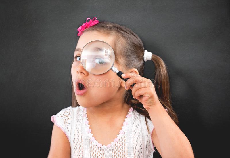 Portrait of Curious Little Child Girl Looking Through Magnifier royalty free stock image