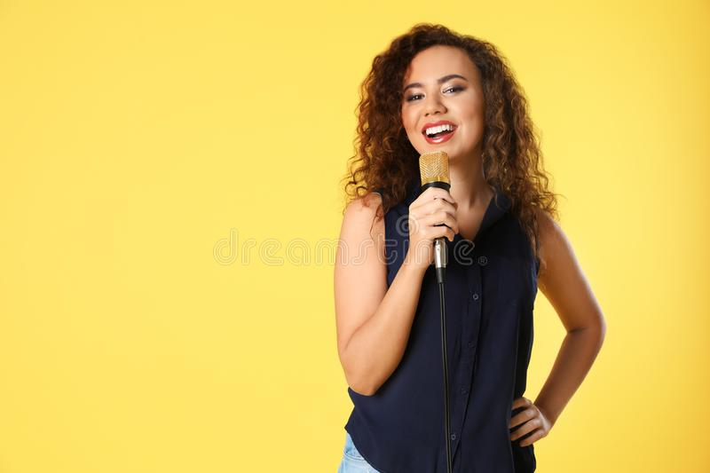 Portrait of curly African-American woman posing with microphone on color background. royalty free stock photography