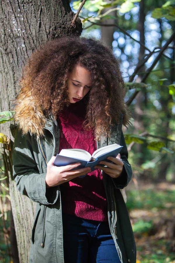 Curly hair teen girl reading book in autumn park royalty free stock photos