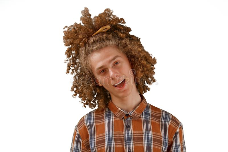 Portrait of a curly-haired young man with a wooden comb in full hair smiling on a white isolated background. male hair care stock image