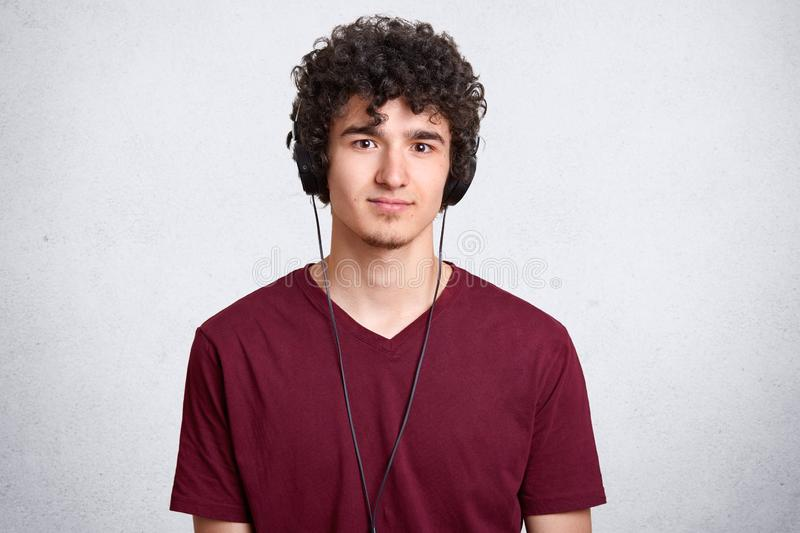 Portrait of curly headed man, wearing casual maroon T shirt, posing in studio while listening to music in headphones, looking at stock images