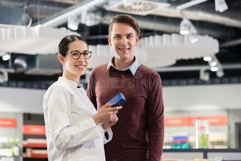 Portrait of a customer standing next to a reliable pharmacist royalty free stock photos