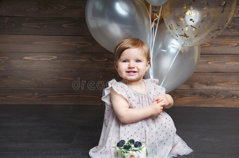 Portrait of cute adorable baby girl celebrating her first birthday with cake and balloons. Looking in camera. First year concept royalty free stock image