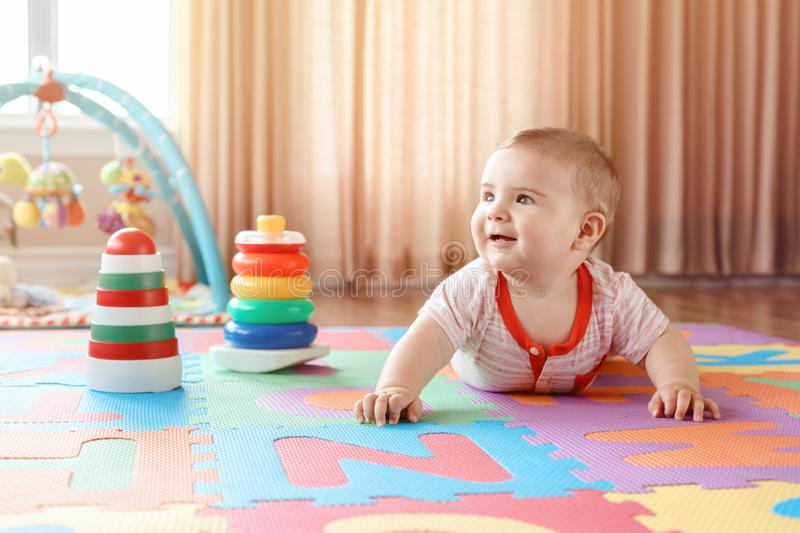 Baby crawling on playmat. Early education development royalty free stock photos