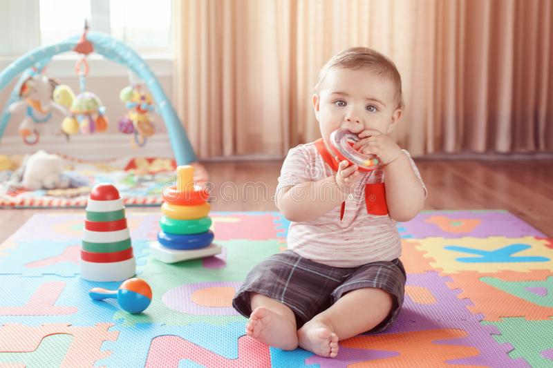 Little baby playing with teething toys chewing ring stock photos