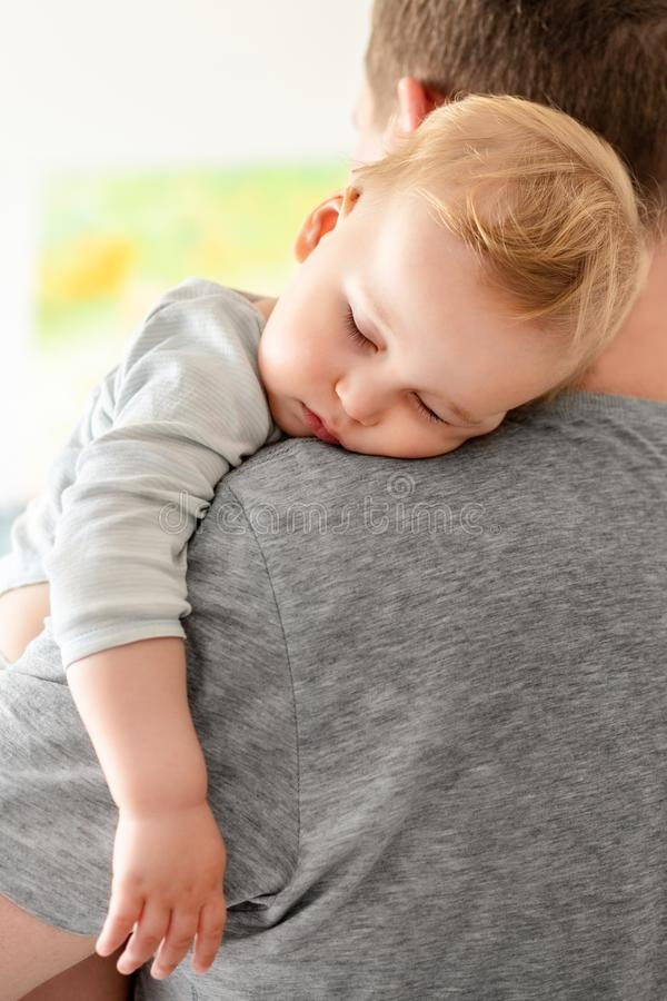 Portrait of cute adorable blond caucasian toddler boy sleeping on fathers shoulder indoors. Sweet little child feeling safety and royalty free stock photography