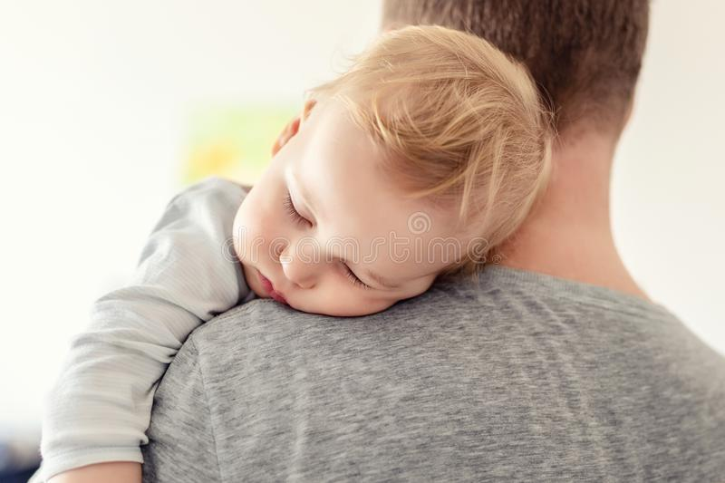 Portrait of cute adorable blond caucasian toddler boy sleeping on fathers shoulder indoors. Sweet little child feeling safety and. Care on daddys hand. Single royalty free stock photos