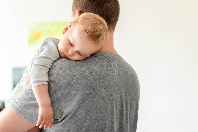 Portrait of cute adorable blond caucasian toddler boy sleeping on fathers shoulder indoors. Sweet little child feeling safety and. Care on daddys hand. Single royalty free stock photography