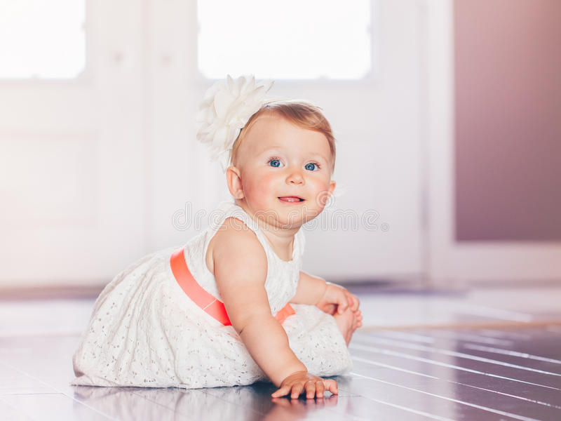 Portrait of cute adorable blonde Caucasian smiling baby child girl with blue eyes in white dress with red bow sitting on floor. Indoors looking in camera stock photography