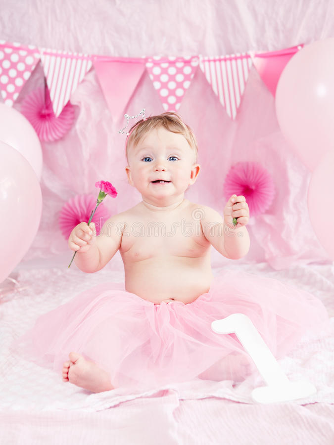 Portrait of cute adorable Caucasian baby girl with blue eyes in pink tutu skirt celebrating her first birthday with gourmet cake stock photography
