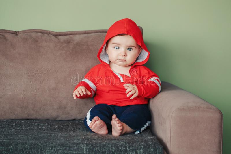 Seven months child sitting on couch at home looking in camera royalty free stock photo