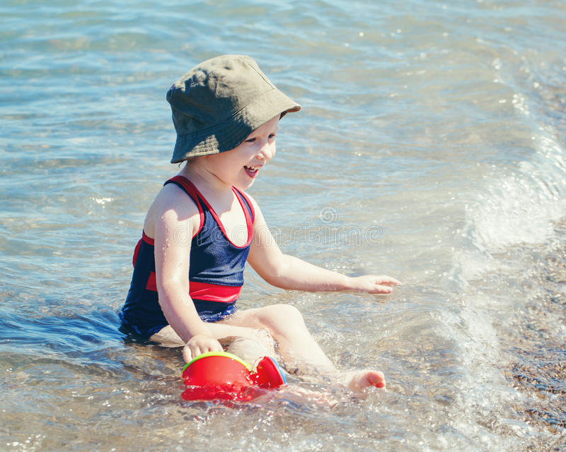 Portrait of cute adorable happy smiling toddler Caucasian girl with hat and watering pot toy on beach sitting in water royalty free stock photo