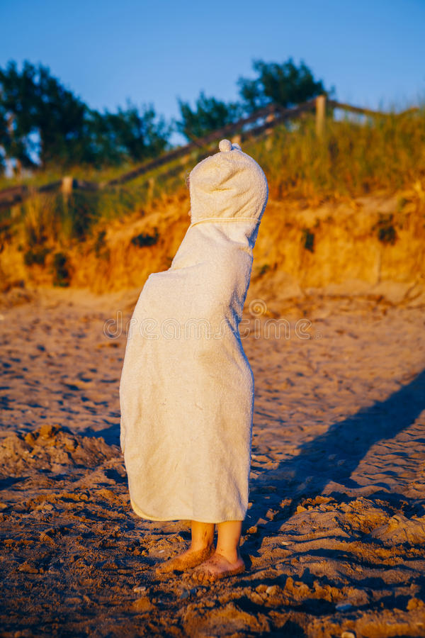 Portrait of cute adorable happy toddler little girl boy with dunes beach towel hiding covering having fun royalty free stock images