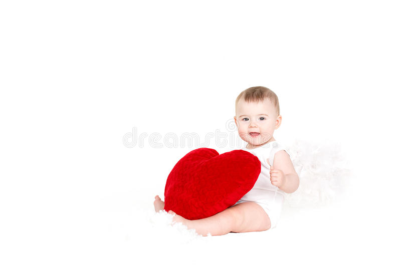 Portrait of a Cute adorable little valentine angel with red soft heart isolated on white background royalty free stock image
