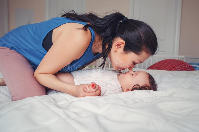 Mixed race Asian mother kissing touching embracing her newborn infant baby stock photo