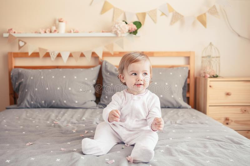 Caucasian blonde baby girl in white onesie sitting on bed in bedroom stock images