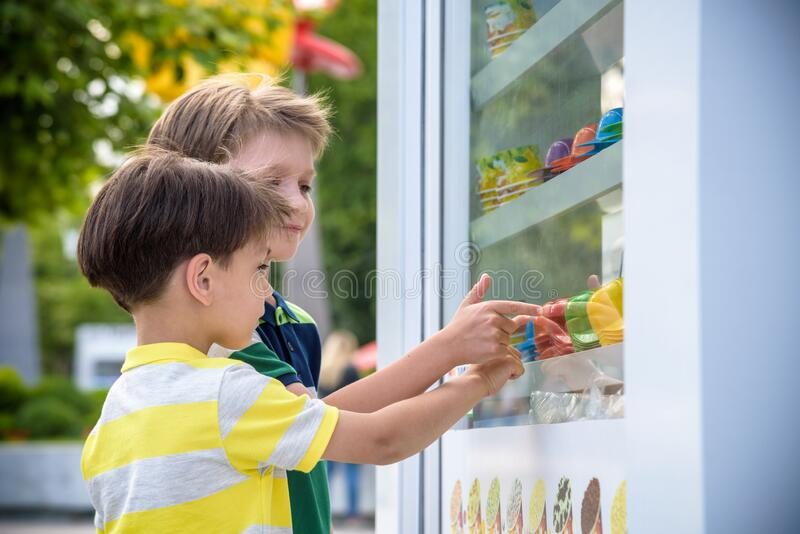 Portrait of cute adorable white Caucasian funny child boy looking at ice cream in shop window, trying to choose one, looking stock image
