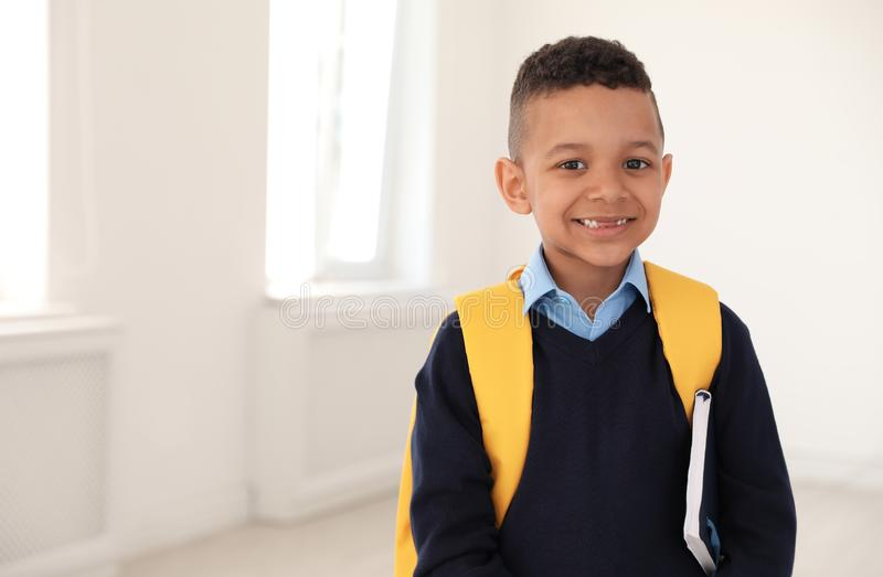 Portrait of cute African-American boy in school uniform with backpack and book indoors stock photo