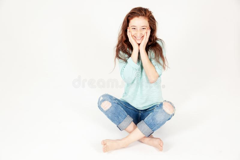 Portrait of cute amusing predronee girl with long dark hair in jeans, sitting on the floor and holding her face, isolated on white royalty free stock photo