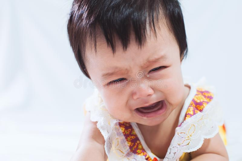 Portrait of cute asian baby girl crying in her bedroom stock images