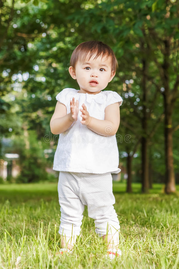 Portrait of cute Asian child clapping her hands royalty free stock image