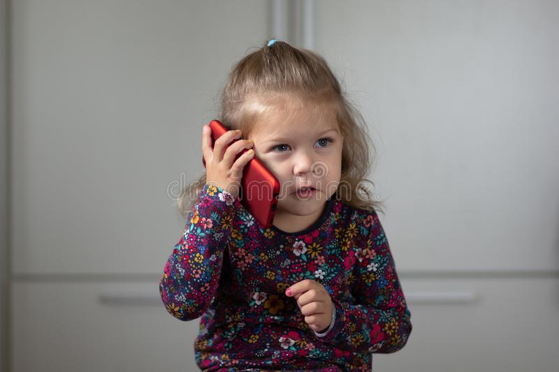 Portrait of cute and attractive child talking on mobile phone looking aside stock photography