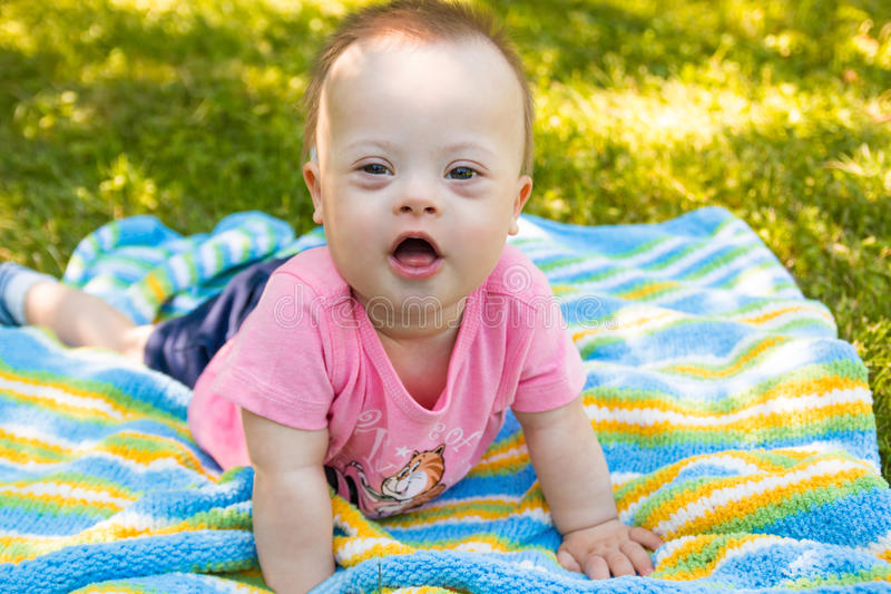 Portrait of Cute baby boy with Down syndrome lying on blanket in summer day on nature. With toys stock photos