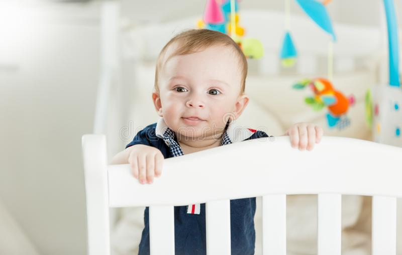Portrait of cute baby boy standing in white wooden crib and looking in camera. Portrait of baby boy standing in white wooden crib and looking in camera stock photography