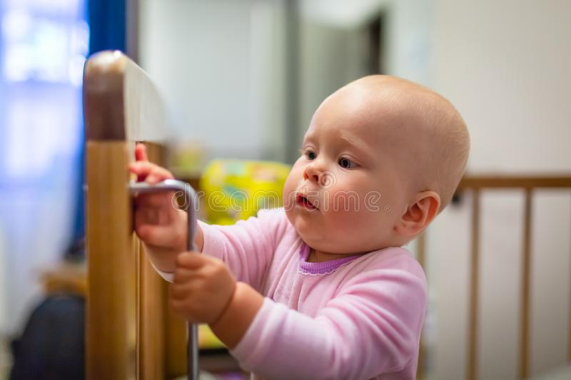 Portrait of cute baby girl with blue eyes is standing in crib. Adorable infant is standing up in cot and is interest royalty free stock image