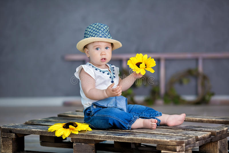 Portrait of a cute baby girl on a light background with a wreath of flowers on her head sitting on sofa basket stock photos