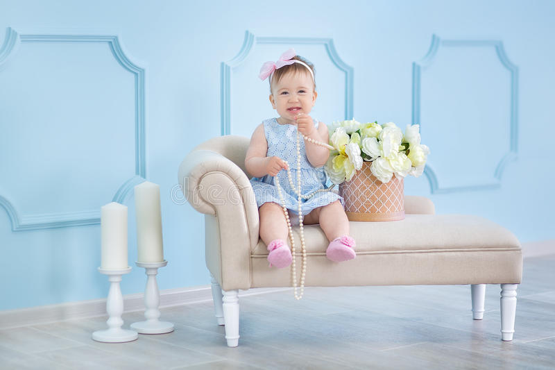 Portrait of a cute baby girl on a light background with a wreath of flowers on her head sitting on sofa basket royalty free stock images