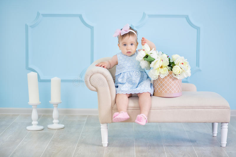 Portrait of a cute baby girl on a light background with a wreath of flowers on her head sitting on sofa basket stock images
