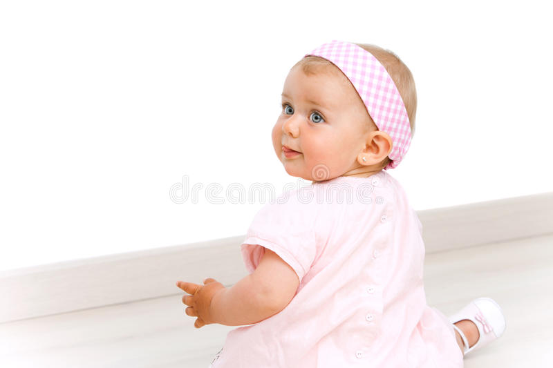 Portrait of cute baby girl with pink head band. Blue eyed baby girl wearing a pink dress and pink head band sitting on the floor stock photography