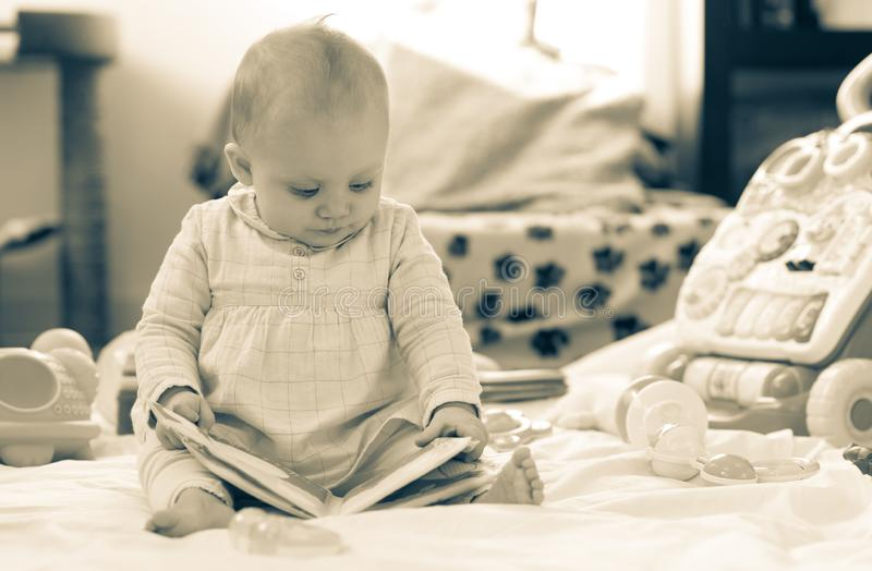 Portrait of cute baby girl with toys, black and white stock photography