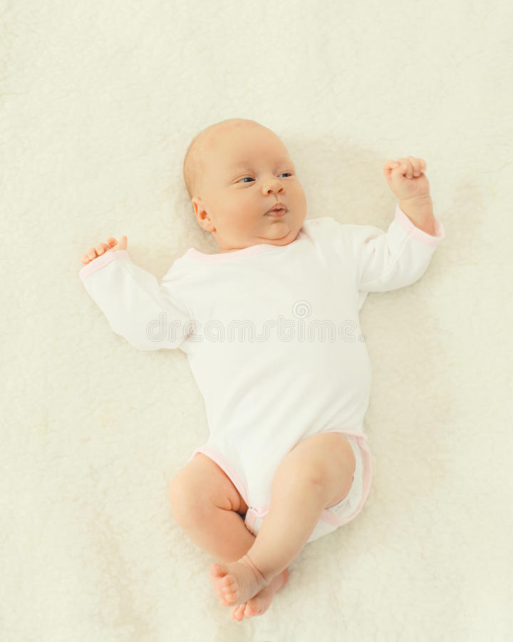 Portrait of cute baby lying on the bed at home royalty free stock image